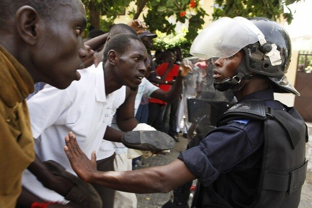 Protestors confront riot police outside the National Assembly during a demonstration in Senegal's capital Dakar