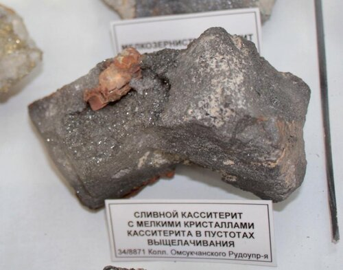 Сливной касситерит с мелкими кристаллами касситерита в пустотах выщелачивания