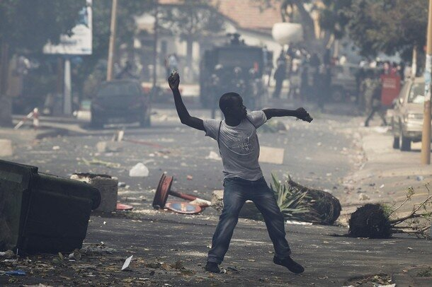A demonstrator throws a rock towards riot police during a demonstration in Senegal's capital Dakar