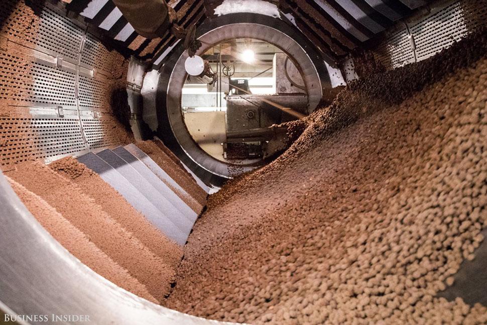 Кусочки шоколада двигаются по охлаждающим тоннелям перед тем, как их покроют разноцветной глазурью.