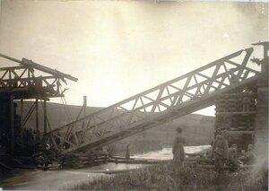 Солдаты поднимают ферму разрушенного моста через реку Бялу.