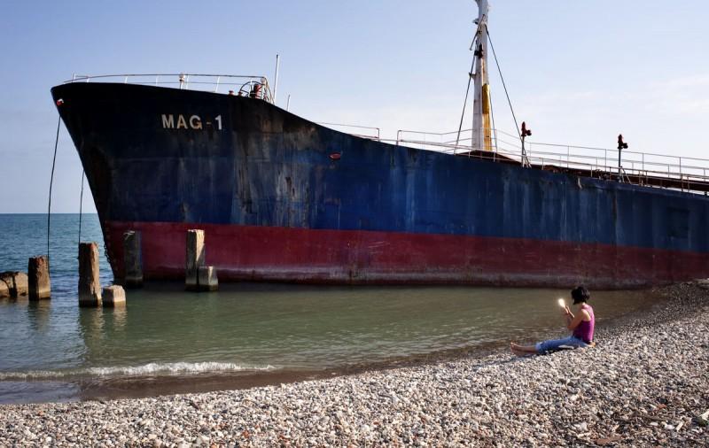 Девушка прихорашивается. На заднем фоне — танзанийский торговый корабль, севший на мель еще в 2010 г
