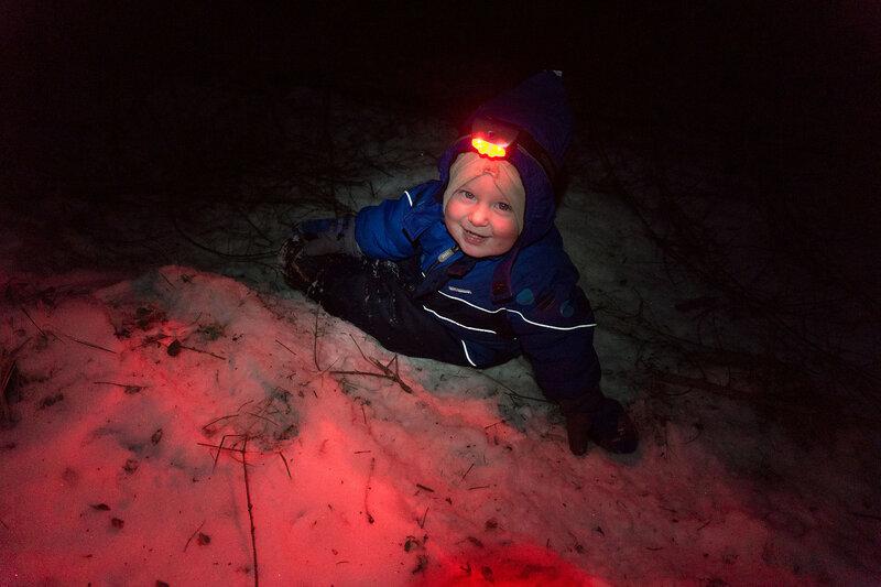 ребенок с налобным фонариком в темноте лесу зимой