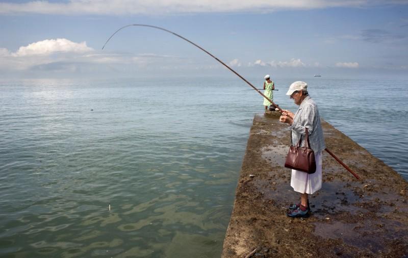 Нина и ее дочь (на заднем плане) рыбачат на пирсе. Нина раньше работала на местном рыбозаводе, разру