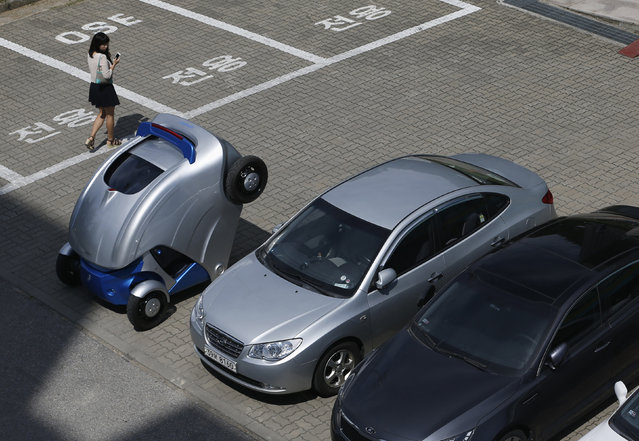 """A woman walks past folded """"Armadillo-T"""", a foldable electric vehicle, at the Korea Advanced Institut"""