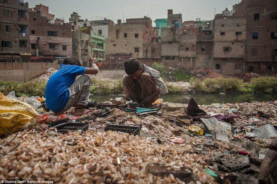 Два мальчика ищут среди мусора ценные металлы, которые они смогут продать.
