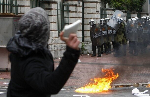 A protester throws a rock at riot policemen during a march by thousands of demonstrators in central Athens