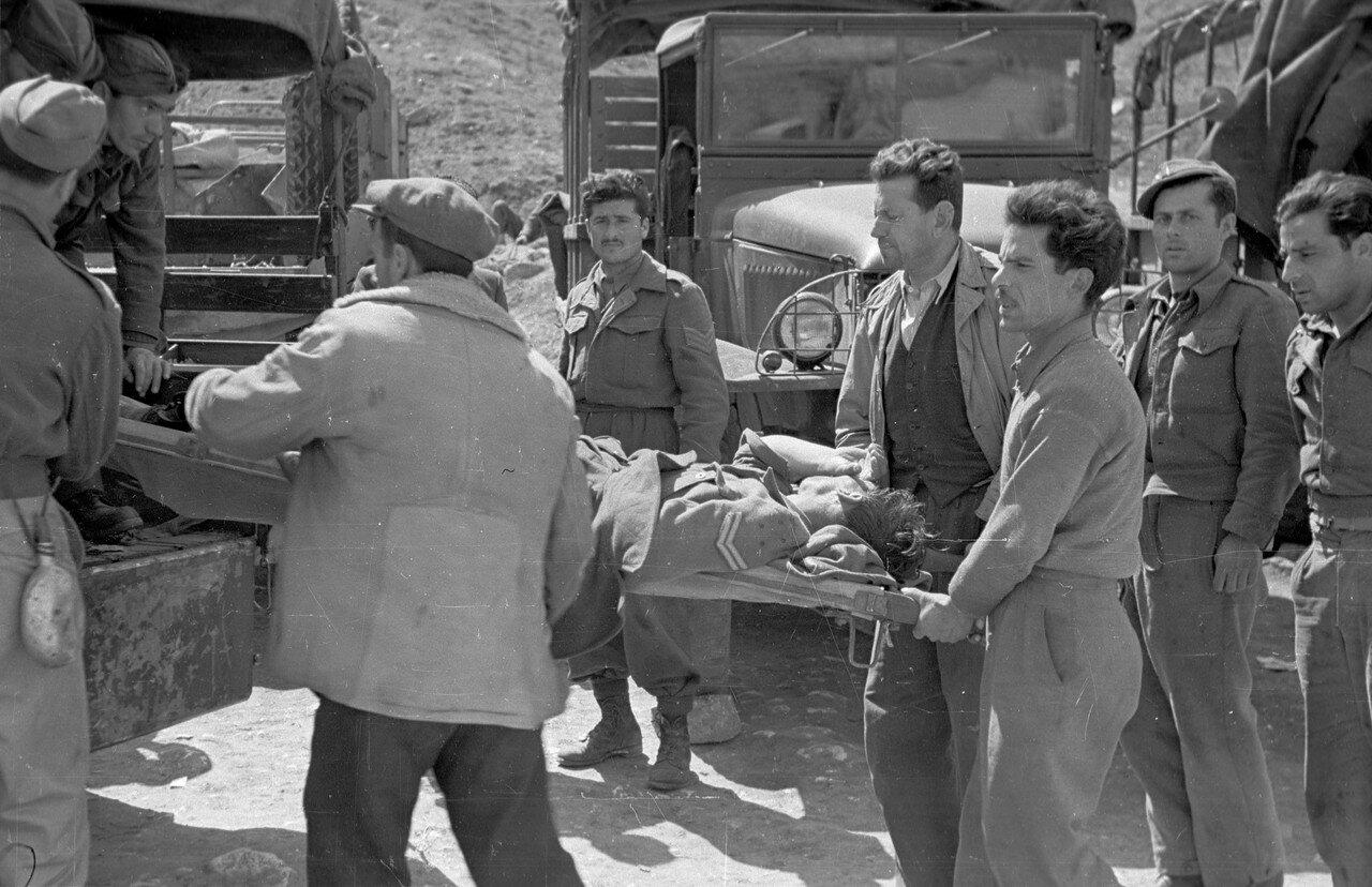 1948. Солдаты переносят раненого на носилках в грузовик 22 мая