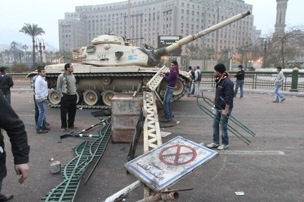 An Egyptian man bulds a barricade in fro