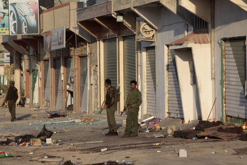 Libyan soldiers loyal to leader Muammar Gaddafi stand at a street littered with rubble in the city of Misrata