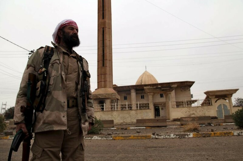 A volunteer from the Yazidi sect who have joined the Kurdish peshmerga forces stand in the street in the town of Sinjar
