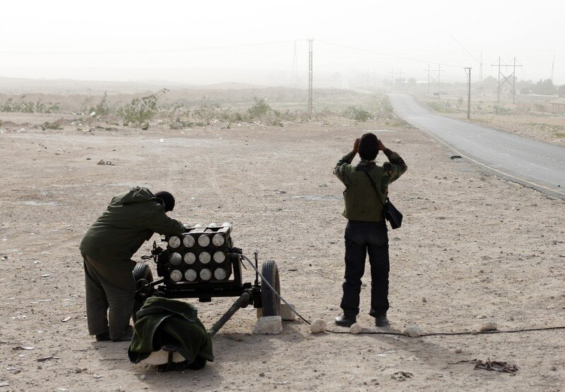 A rebel aims a multiple rocket launcher in Brega
