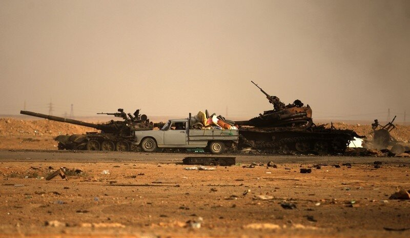 Displaced Libyans drive past wrecked tan