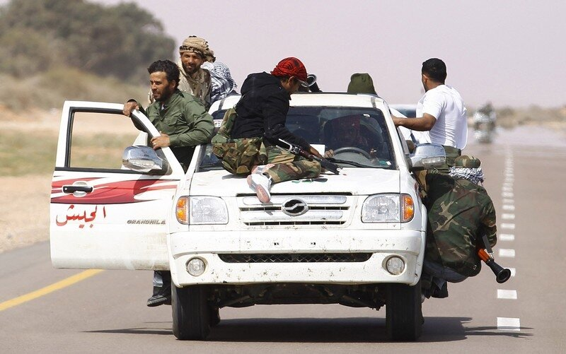 Rebel fighters beat a hasty retreat after encountering a Libyan Army ambush on the road between Bin Jawad and Nawfiliyah