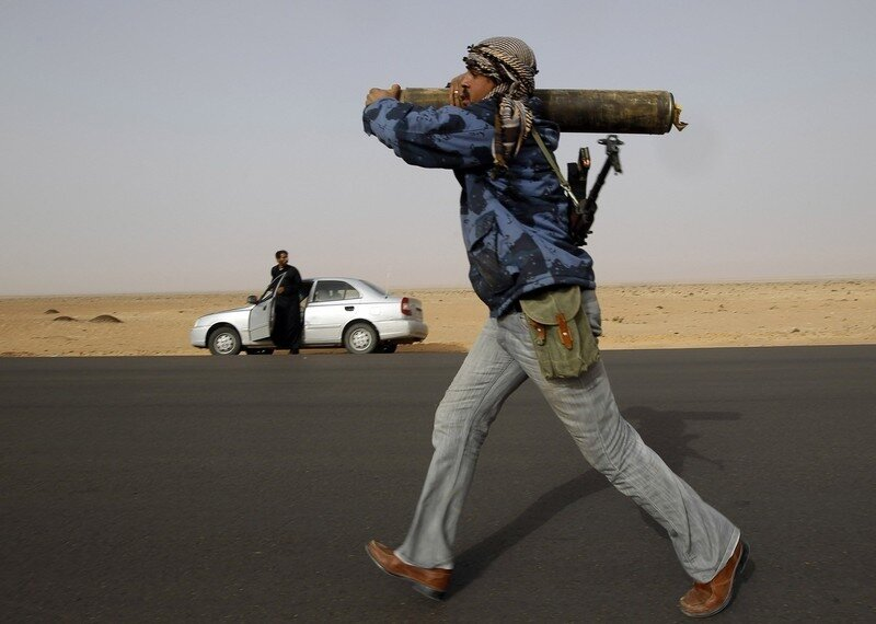 A rebel fighter carries a shell as he runs during a battle near Ras Lanuf