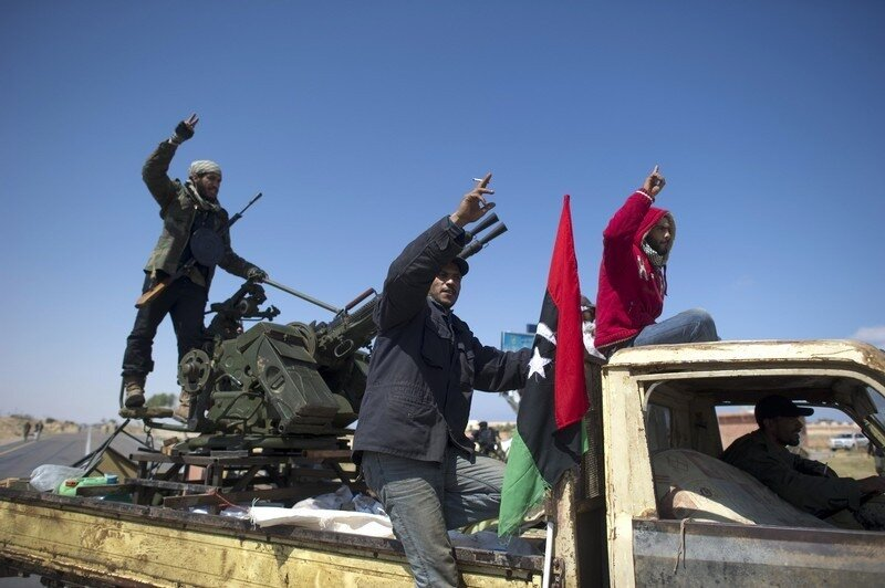 Rebel fighters flash the victory sign as