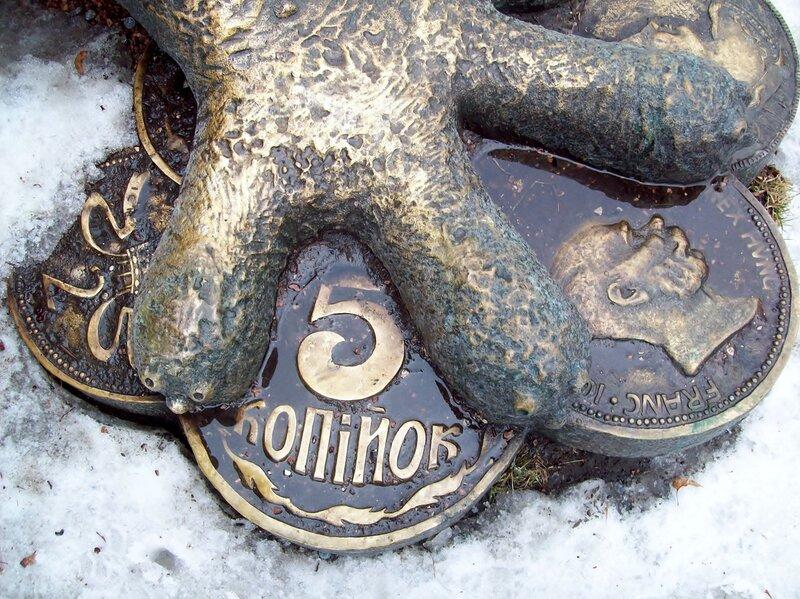Жаба стоит на монетах