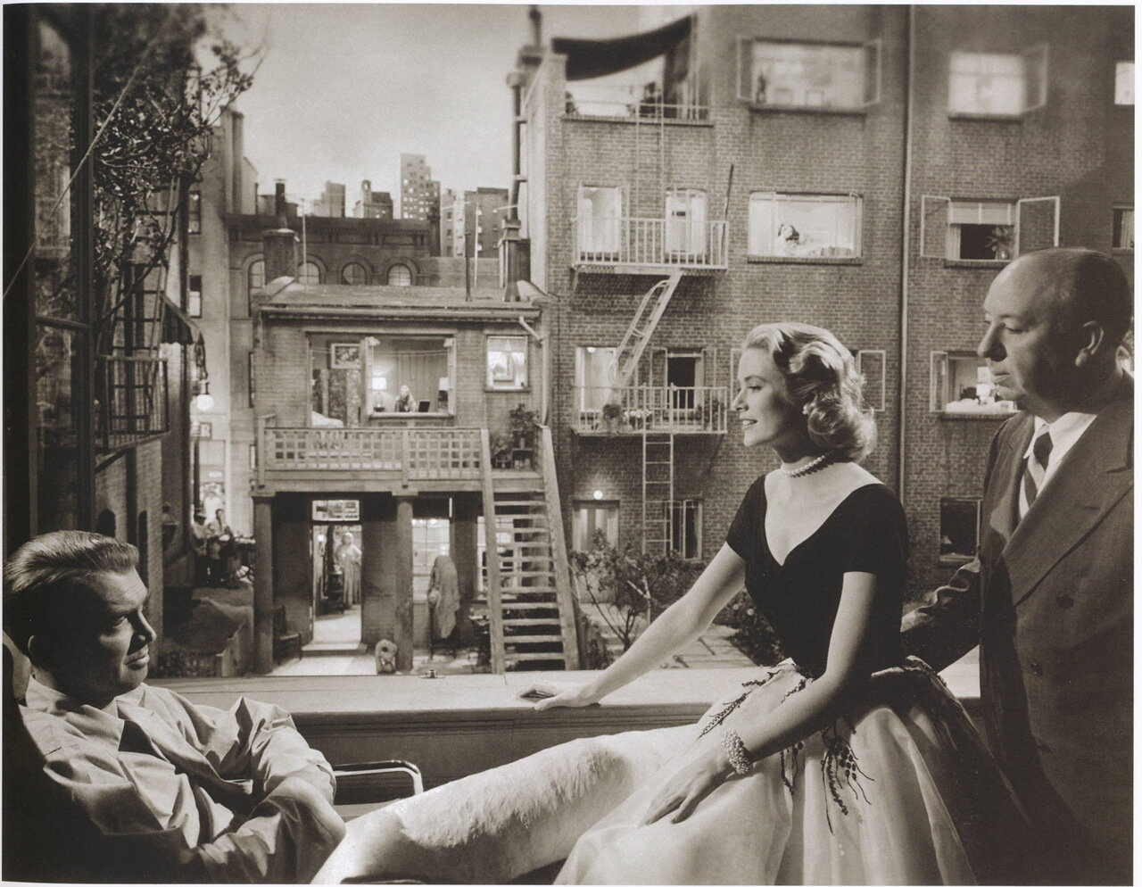 Jimmy Stewart,  Grace Kelly and Alfred Hitchcock pose for commercial poster Rear Window, a film directed by Alfred Hitchcock in 1954.