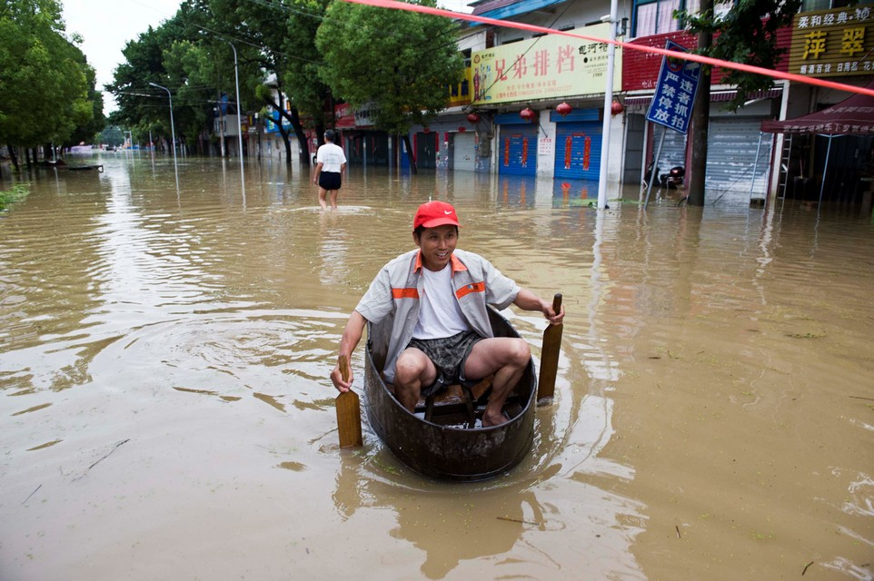 A resident rows a makeshift boat to make his way at a flooded street in Chaohu