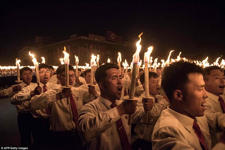 Участники шествия с факелами поют песни после завершения XVII съезда Трудовой партии Кореи. Съезд па