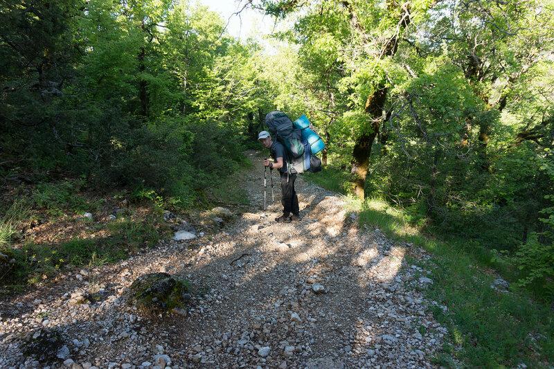 пеший турист с рюкзаком на тропе приют Астрака - деревня Микро Папиго