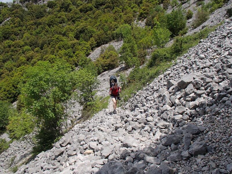 мама с ребенком идут по каменной осыпи на тропе в ущелье Викос