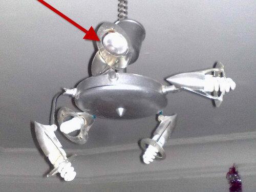 Фото 2. В люстре, представляющей из себя объединение пяти спотов, осталась лишь одна специализированная лампа (указана тёмно-красной стрелкой), остальные заменены КЛЛ.