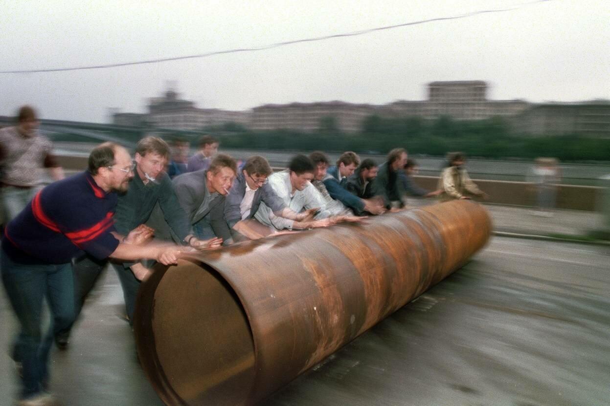 19 августа 1991. Сторонники президента России Бориса Ельцина катят большую металлическую трубу, чтобы использовать  ее на баррикадах у Белого дома.