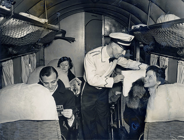 Eastern Airlines steward Charles Burns, a member of the first class of male attendants aboard a domestic airline, helps a passenger at Newark Airport.jpg