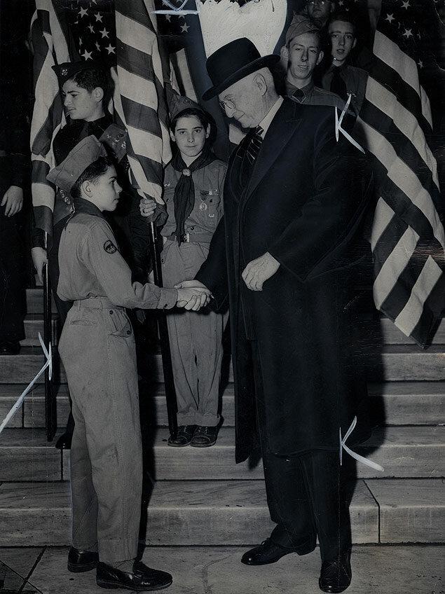 Elder statesman Bernard Baruch and Boy Scout William C. Schirmann, Jr., shake hands during Flag Day ceremonies on the steps of the New York Public Library.jpg