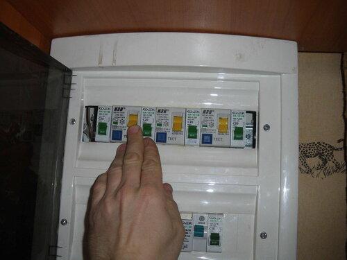 Фото 10. Электрик в квартирном щите включает группы, защищённые устройствами защитного отключения (УЗО).