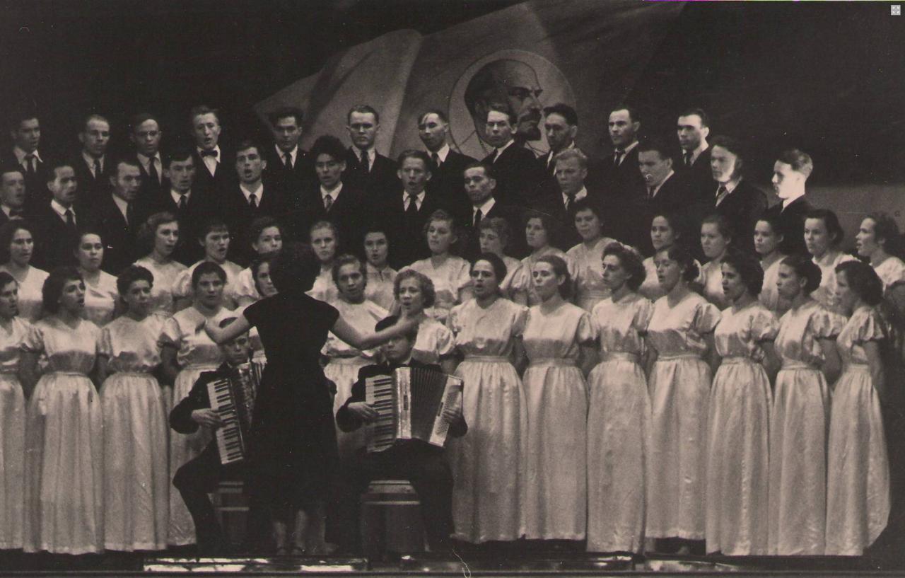 Хор цеха №4 (нач.Князьков Л.И.) выступает на 6-м заводском смотре художественной самодеятельности. Руководит хором Т.И.Широкова 1960 г.