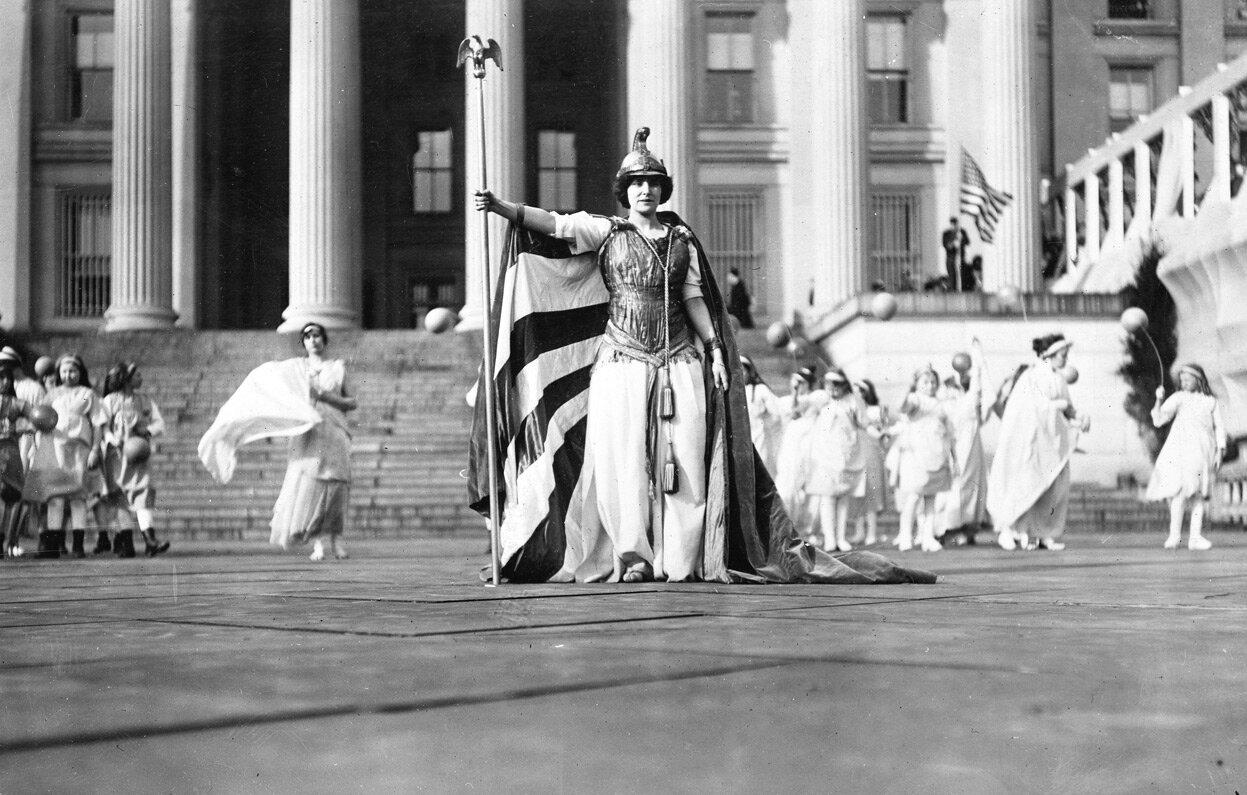 Немецкая актриса Хедвига Рейхер в костюме «Columbia» участвует в театрализованной постановке за женское избирательное право перед зданием Казначейства в Вашингтоне, округ Колумбия, 3 марта 1913.