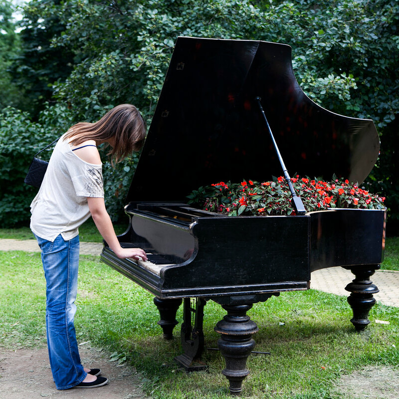 woman playing on an old piano, standing in the garden. The piano is used for landscaping. Inside the piano growing begonia.