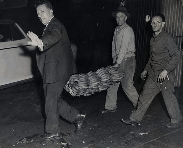 People make off with discarded bananas which were being thrown overboard from a ship docked at Pier 58