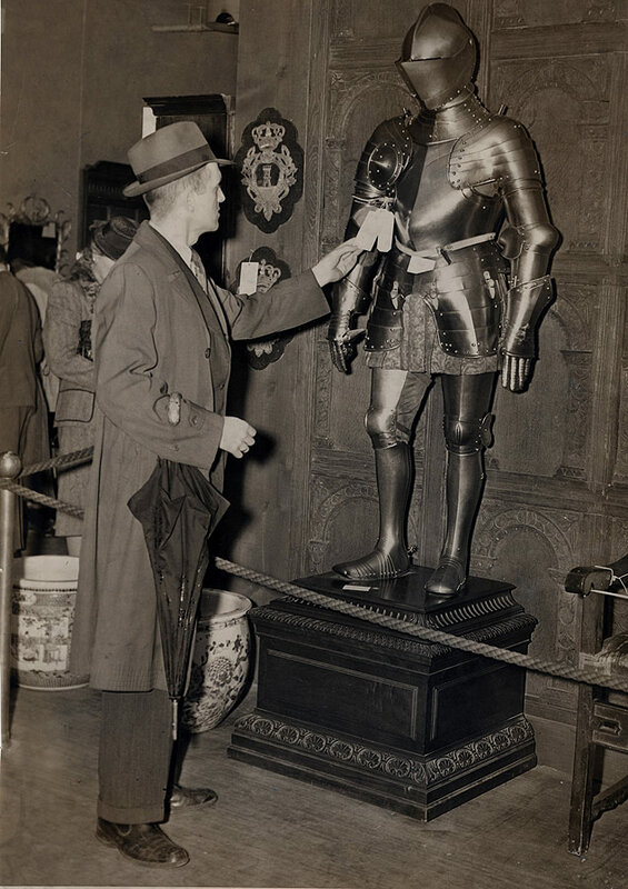 A potential buyer inspects a suit of Middle European armor from the 16th century prior to the Clarence Mackay Sale at Gimbels