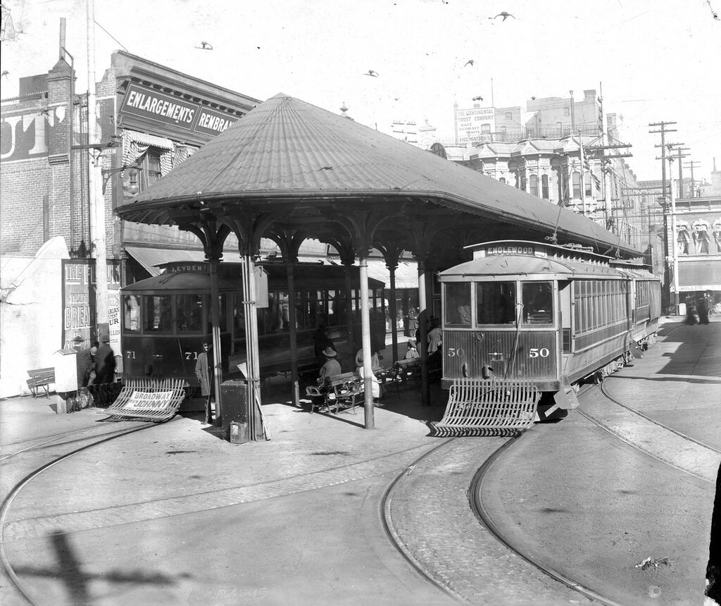 Denver Tramway Company trolley cars Englewood #50 and Leyden #71 are parked at a covered stop on 15th Street in Denver, Colorado, between 1900 and 1905