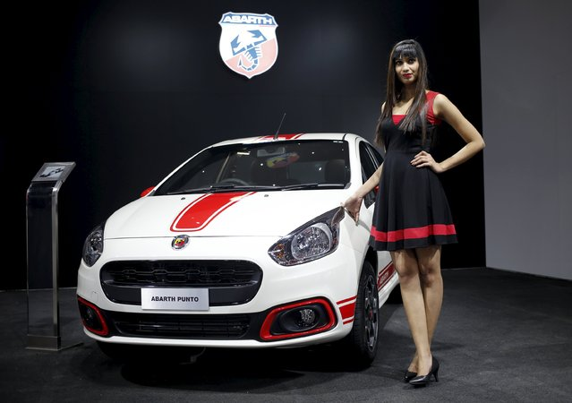 A model poses next to a Fiat Abarth car on display at the Indian Auto Expo in Greater Noida, on the