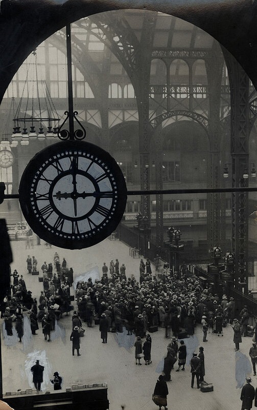 The station clock overshadows commuters in Penn Station