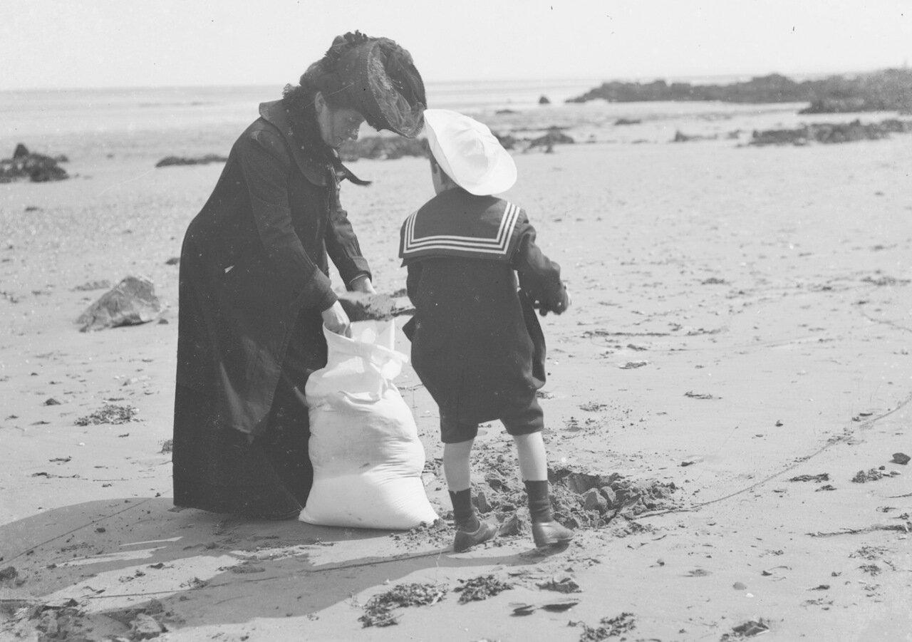 Мама с сыном собирают песок. 1904.