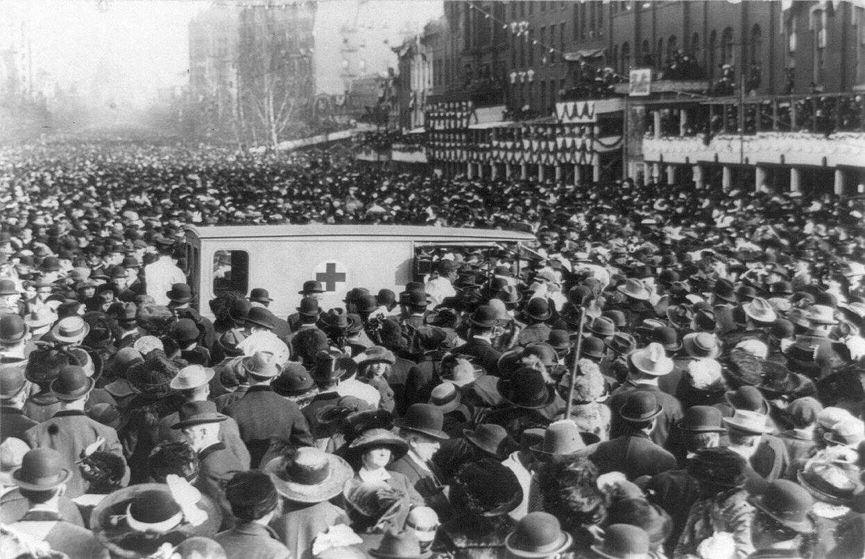 Толпы окружает скорую помощь. Десятки демонстрантов были ранены в тот день во время шествия, 3 марта 1913 года