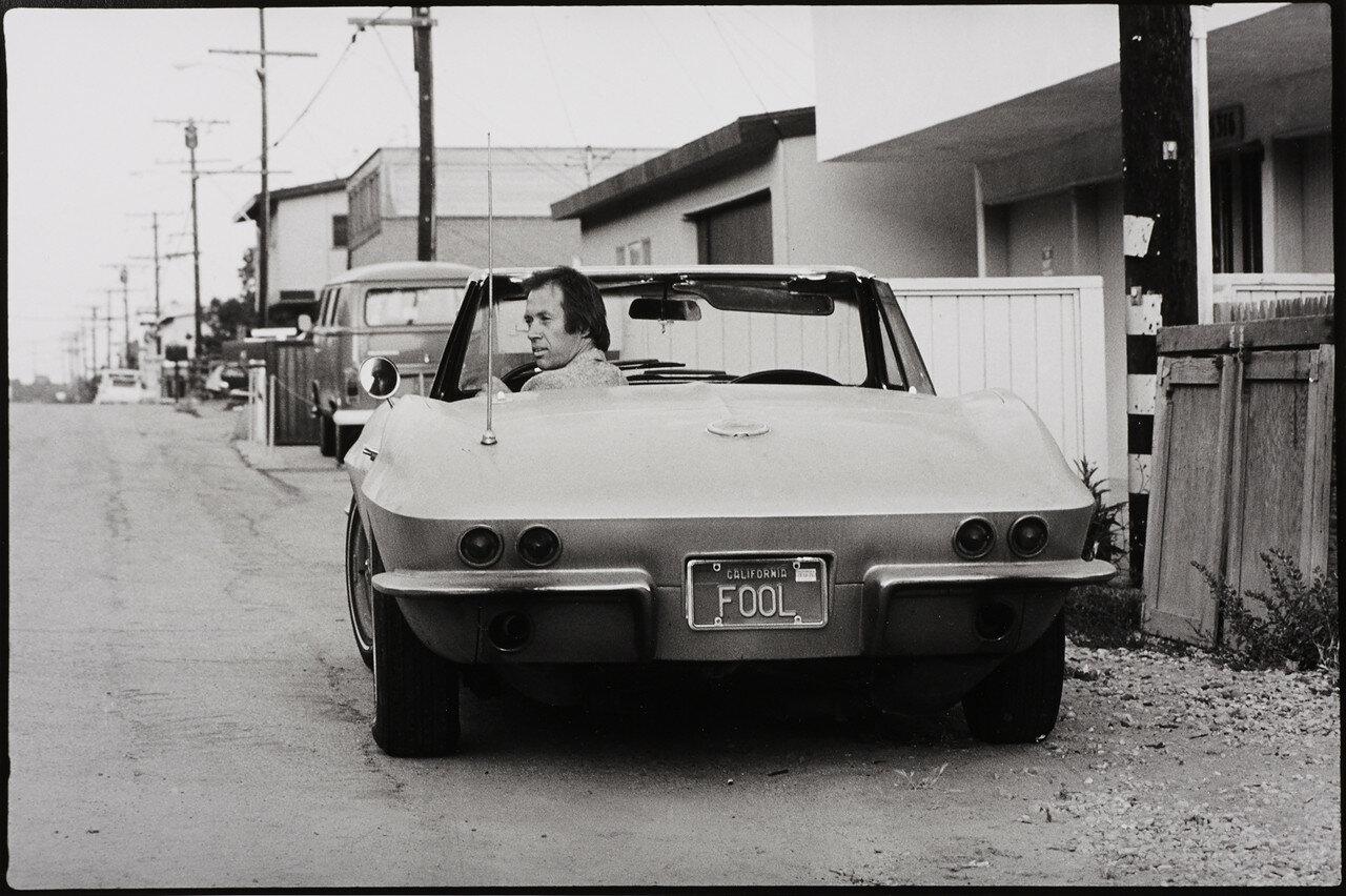 1975. Дэвид Кэррадайн в своей машине с номерным знаком «дурак», Калифорния