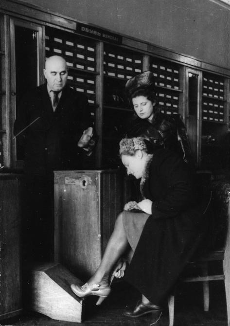 1947. Примерка обуви в обувном отделе Центрального универмага в первый день торговли после отмены карточек