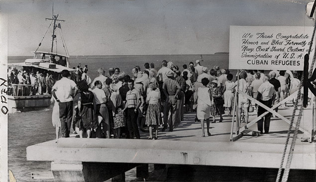 Beneath a welcome sign on the Key West, Florida, dock, Cuban exiles prepare to greet another boatload of evacuating Cuban refugees
