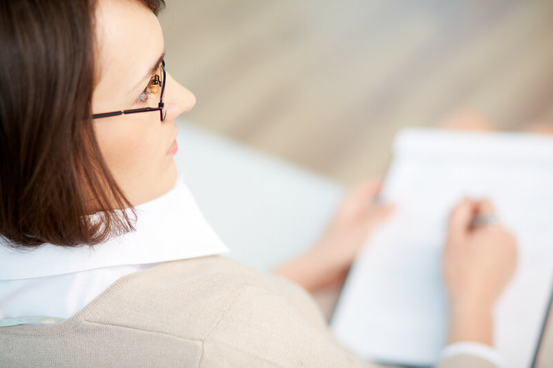 Professional psychiatrist keeping record during therapy session