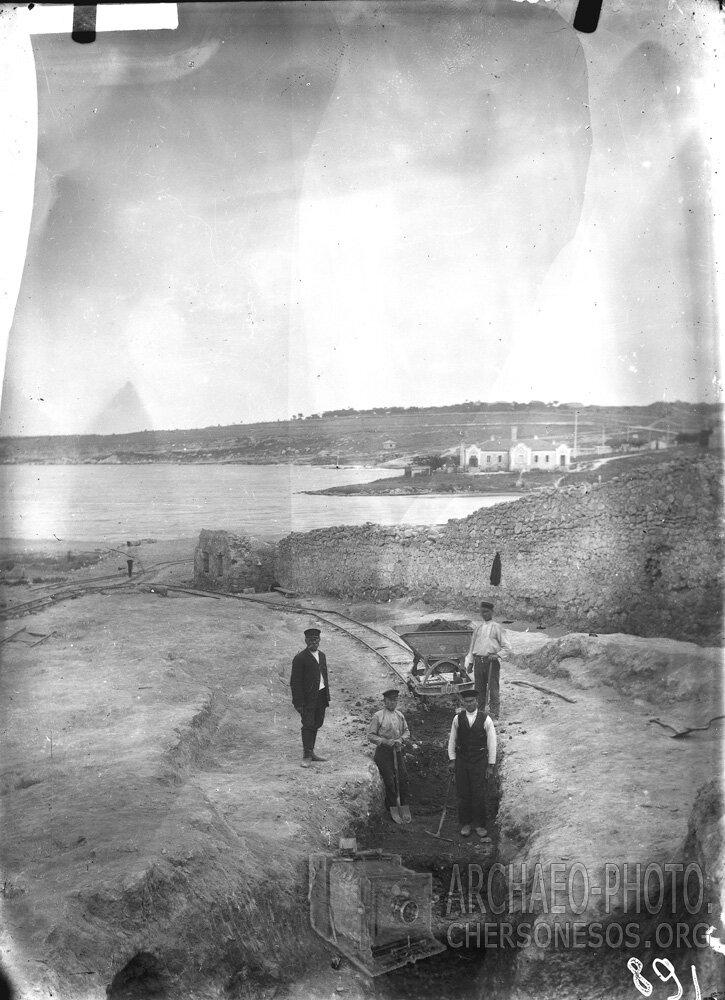 Рабочие с вагонеткой на раскопках у оборонительных стен близ Карантинной бухты