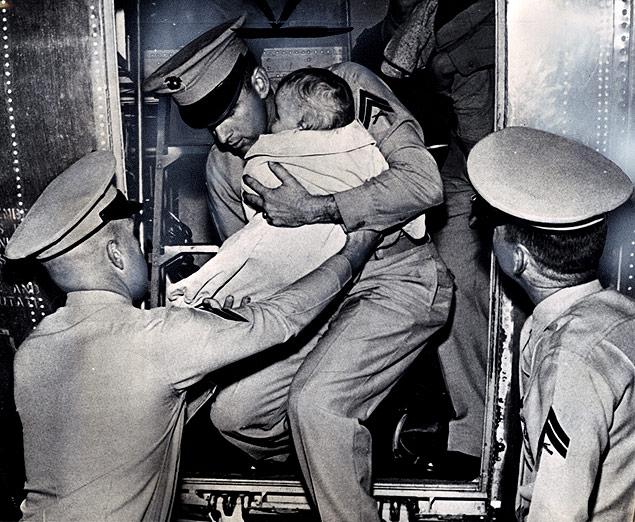 Marines disembark at Nrofolk, Virginia, with a baby evacuated from Guantanamo during the Cuban Missile Crisis