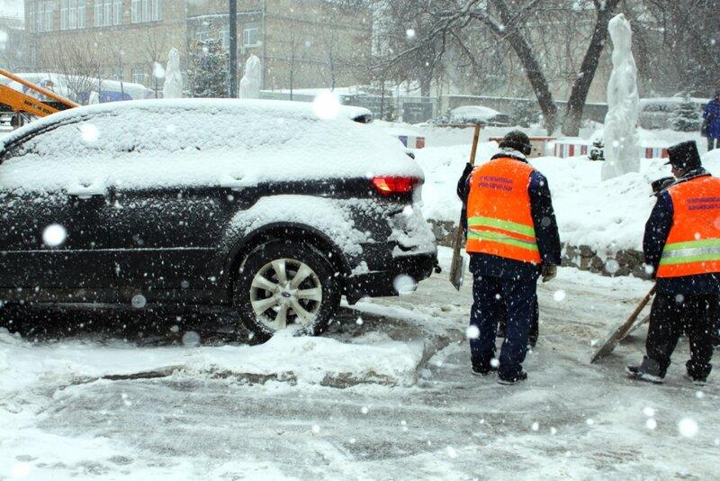 Дорожные рабочие чистят лед вокруг автомобиля