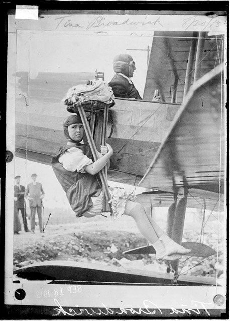 Photograph of Tina Broadwick, parachute jumper, sitting in a sling on the side of an airplane.
