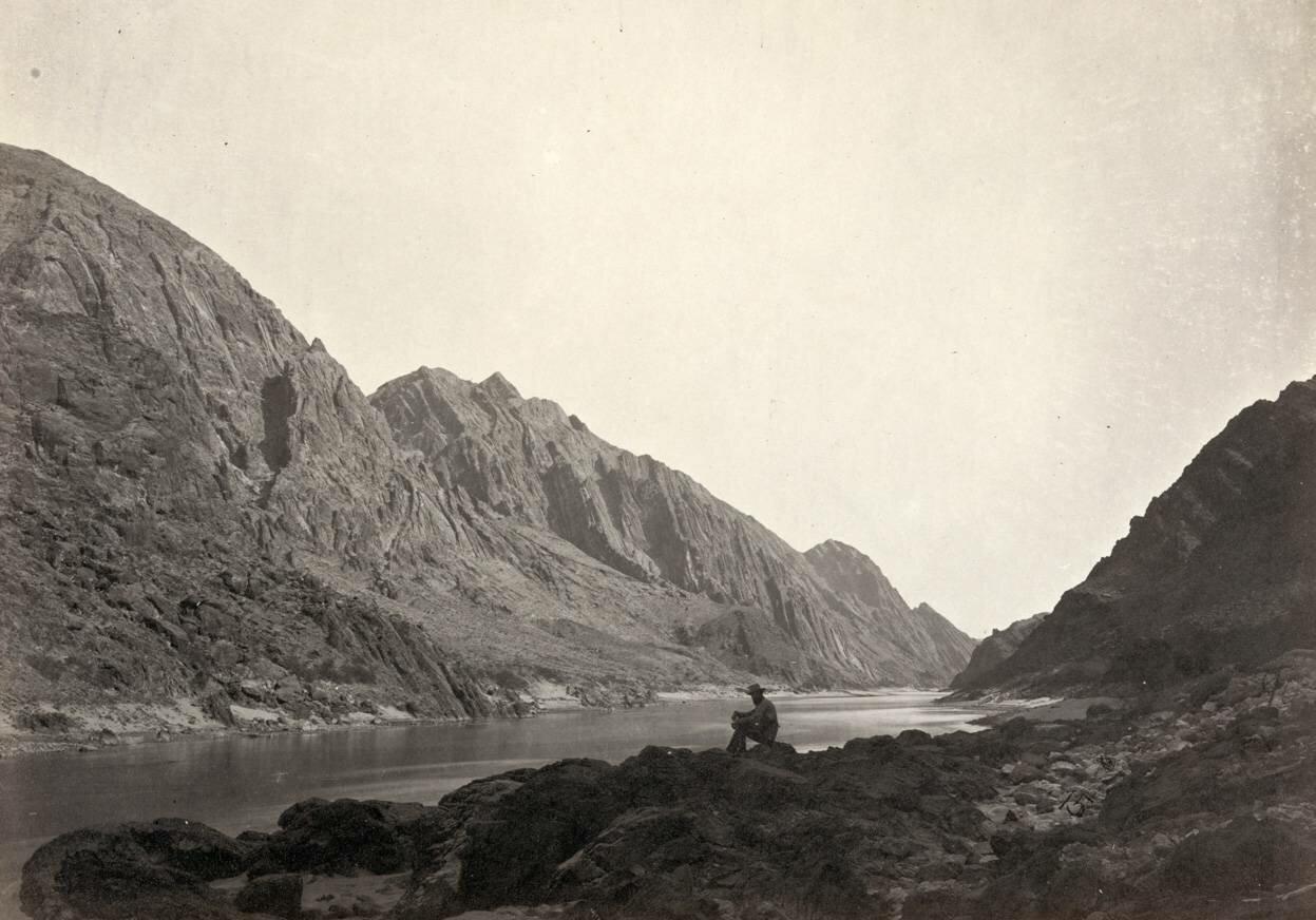 Мужчина сидит на скалистом берегу возле реки Колорадо в каньоне Айсберг, на границе графства Мохаве, штат Аризона, и округа Кларк, штат Невада в 1871 году.